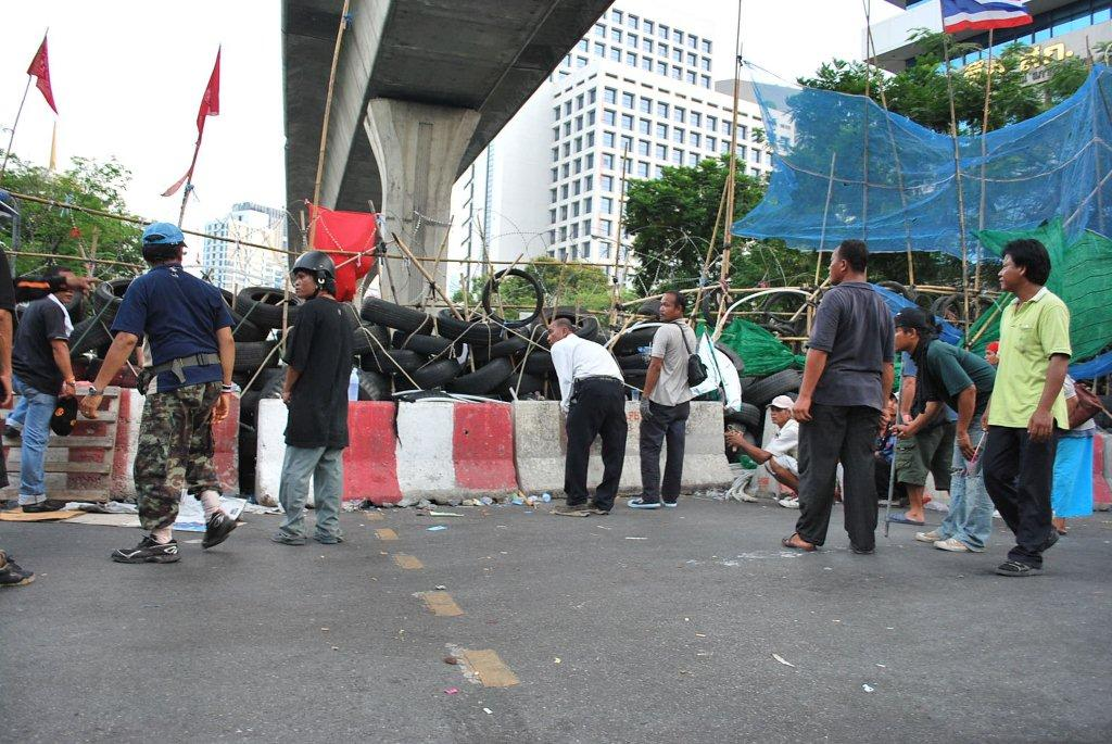 Redshirts crouch as shots ring out close to Chulalongkorn Hospital on Saturday afternoon. (Photo: Simon Roughneen)