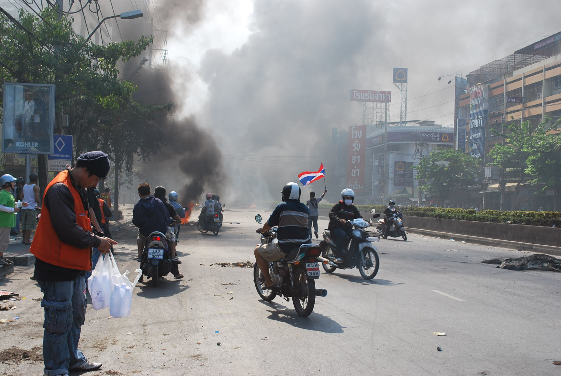 After series of shooting and explosions on Sat. afternoon, protestors run out to taunt the troops from behind the smokescreen. (Photo: Simon Roughneen)