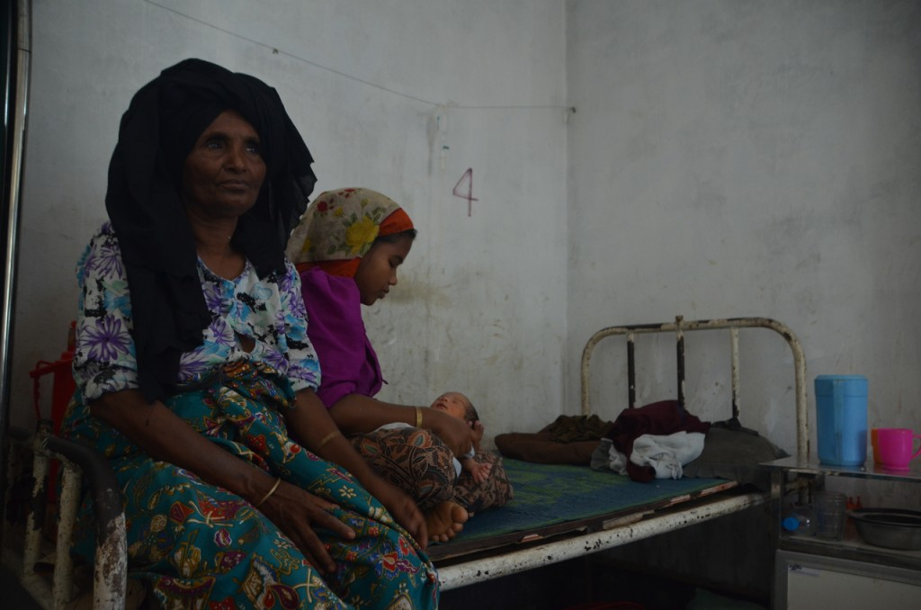 Anuar Begum and child sit behind Anuar's mother Zeinab, inside clinic at Thay Chaung (Photo: Simon Roughneen)