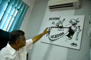 Cartoonist Zunar discussing one of the drawings that angered the Malaysian government, depicting a defence ministry procurement scandal (Photo by Simon Roughneen)