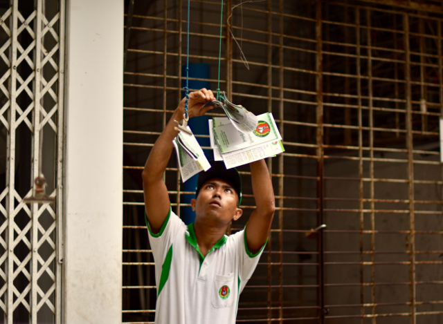 A canvasser for the USDP distributes leaflets to residents in downtown Yangon a week before the Nov. 8 2015 elections. (Photo by Simon Roughneen)