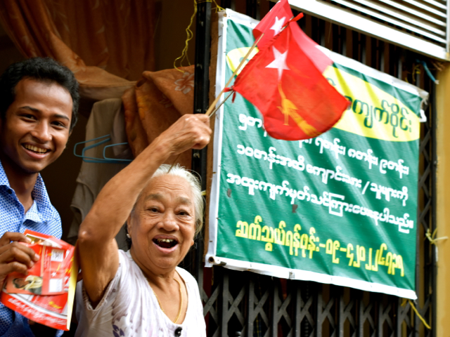Residents of Thingyangun in Yangon cheer as NLD candidates go on walkabout in the district on Oct 13 (Photo: Simon Roughneen)