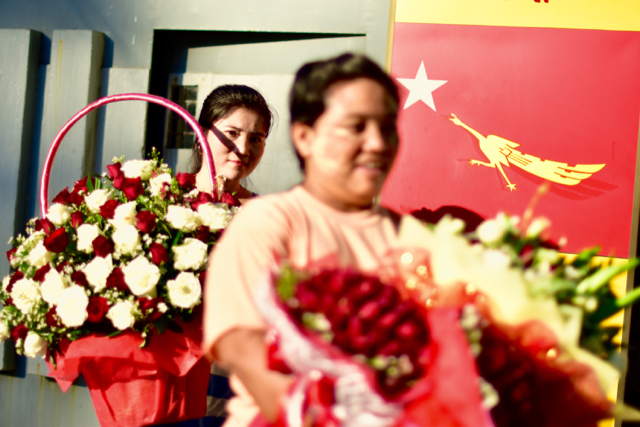 NLD supporters carry flowers from Aung San Suu Kyi's house on Nov. 12 (Photo: Simon Roughneen)