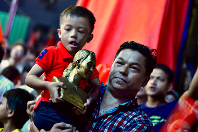 Father and son holding statuette of Aung San Suu Kyi, the NLD leader, outside the party's headquarters on Nov. 8 (Photo: Simon Roughneen)
