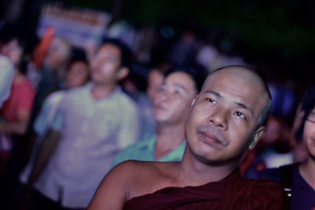 A Buddhist monk stood among NLD supporters outside the party's headquarters as vote counting started on Nov. 8. (Photo by Simon Roughneen)
