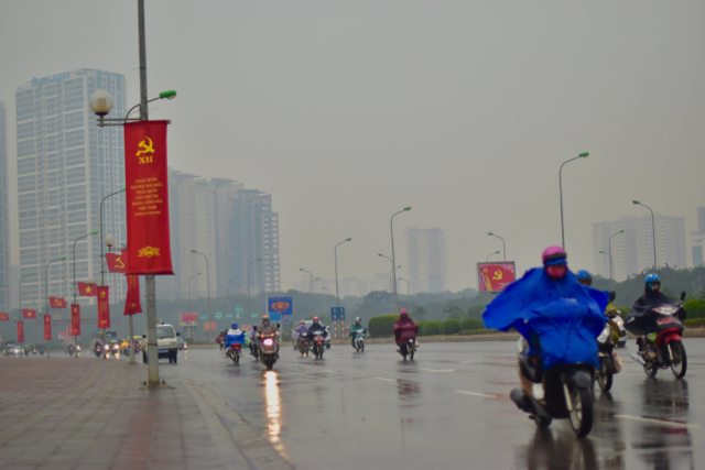 Motorcyclists brave the winter rain as they ride past the My Dinh National Convention Center in Hanoi, the Congress venue. (Photo: Simon Roughneen)