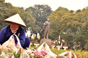 Despite Vietnam turning to free trade, communist flags, murals and statues are common, especially in the capital Hanoi. Here a gardener tends to flowers close to a statue of Lenin in Hanoi. (Photo: Simon Roughneen)