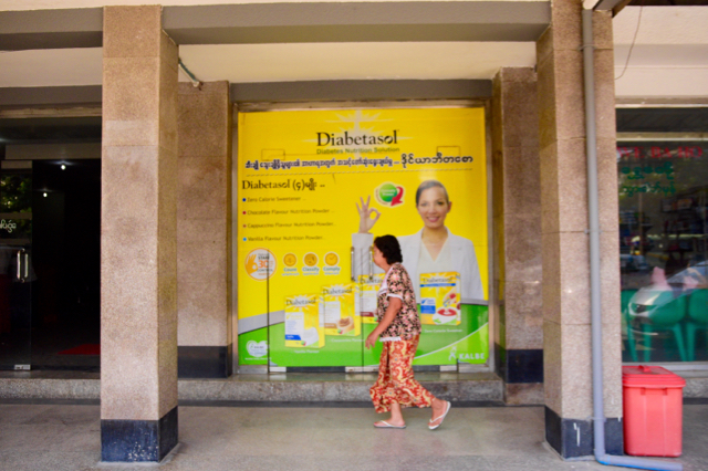 Woman walks past advertisement for diabetes medication at Shwe Baho Hospital in Yangon (Photo: Simon Roughneen)