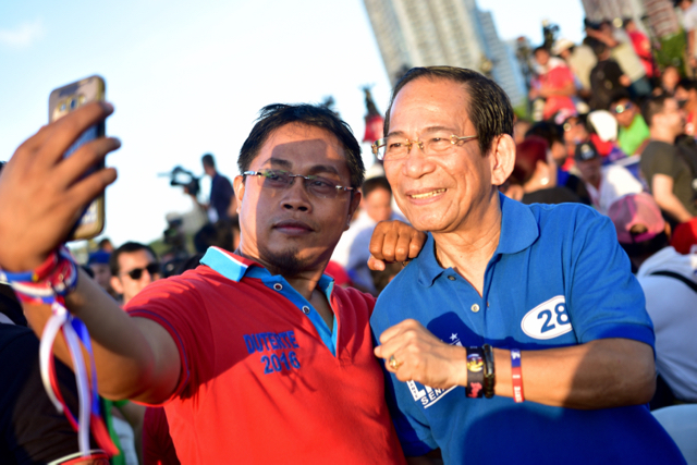 Senate candidate Dante Liban (blue tshirt) poses with supporter of Rodrigo Duterte at Rizal Park in Manila on May 7 (Photo: Simon Roughneen)