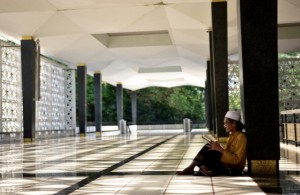Reading Islamic verse at the national mosque in Kuala Lumpur (Photo: Simon Roughneen)