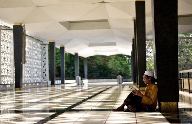 Reading Islamic verse at the national mosque in Kuala Lumpur (Photo: Simon Roughneen)