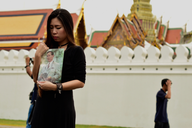 Mourners, many bearing images of King Bhumibol Adulyadej, have been gathering in front of the Grand Palace in Bangkok to pay respects (Photo: Simon Roughneen)