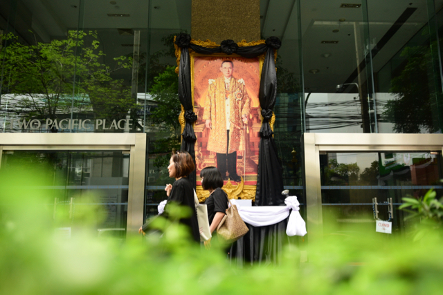 Thais clad in black walk past an image of the late King Bhumibol Adulyedej on one of Bangkok's main streets (Photo: Simon Roughneen)