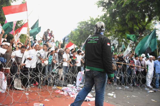 Protestors at the barbed wire and police barricade erected in front of Indonesia's presidential palace (Photo: Simon Roughneen)