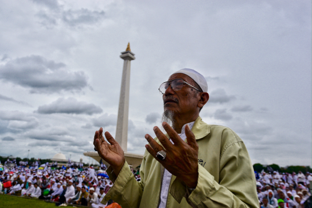 Protestor praying during Dec. 2 2016 Islamist protest against the Jakarta governor, a Chinese-Indonesian Christian known by his nickname ' Ahok.'  In the background is Indonesia's National Monument, or Monas (Photo: Simon Roughneen)