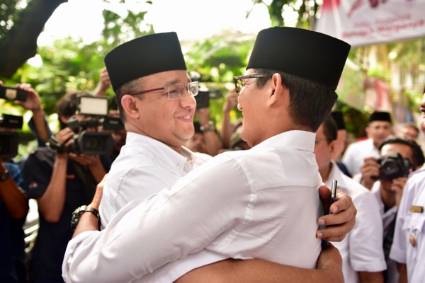 The winner of Jakarta's gubernatorial election Anies Baswedan (left) embraces running-mate Sandiaga Uno at their campaign headquarters in central Jakarta on April 19 (Simon Roughneen)