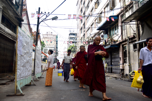 Buddhist monks on alms collection duties walk past a polling center in Yangon on April 1 (Photo: Simon Roughneen)