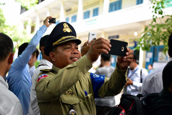Policeman photographing Cambodia's current main opposition leader Kem Sokha at a polling center at Chak Angre Leu pagoda in Phnom Penh on June 4 (Photo: Simon Roughneen)