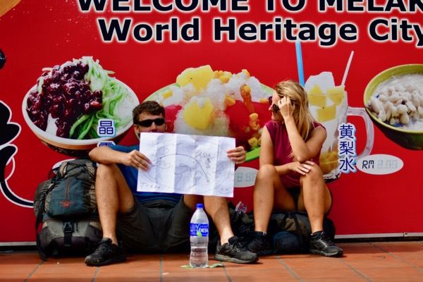 Backpackers on Jonker Street in Melaka, soliciting donations to fund their travels around Asia (Simon Roughneen)