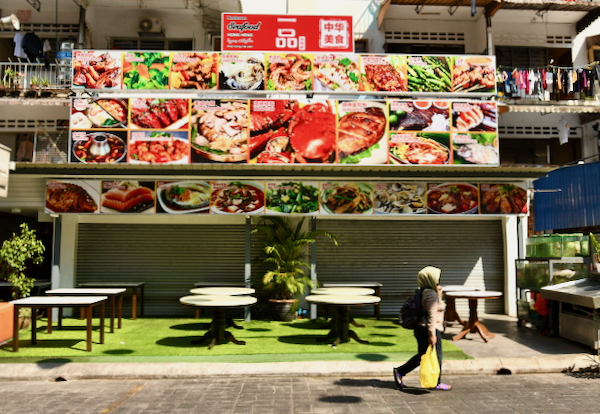 Woman walks past a restaurant in Kuala Lumpur after the government imposed a 2-week anti-virus lockdown on March 18 (Simon Roughneen)