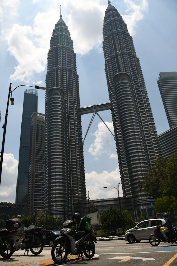 Food delivery couriers - such as this one stopping in the shade of Kuala Lumpur's Petronas Towers - were busy around Kuala Lumpur on Wedneday with restaurants are limited to takeaway or delivery and citizens urged to stay at home during Malaysia's part-lockdown (Simon Roughneen)