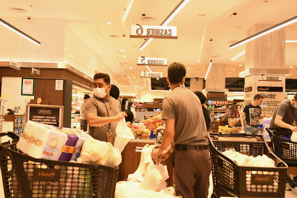 Staff at a supermarket check-out in Kuala Lumpur, one of the types of businesses open during Malaysia's lockdown (Simon Roughneen)