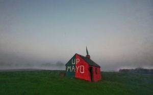 Roadside building in Manulla, Co. Mayo, painted in the colours worn by the county's Gaelic football team. Taken in evening fog on December 7 2020, the day after the team qualified for a 5th All-Ireland football final in 9 years (Simon Roughneen)