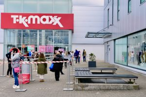 Businesses such as this retailer in Ireland have been foced to close by pandemic restrictions. Patrons seen here lining up to enter after the end of Ireland's third lockdown in May 2021 (Simon Roughneen)